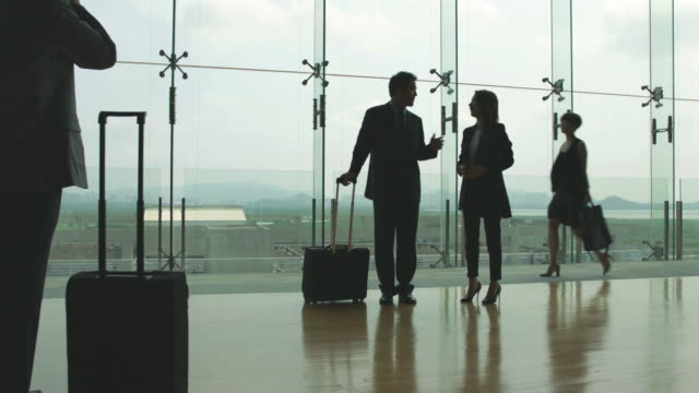 asian businessman and businesswoman talking in airport - business travel stock videos and b-roll footage