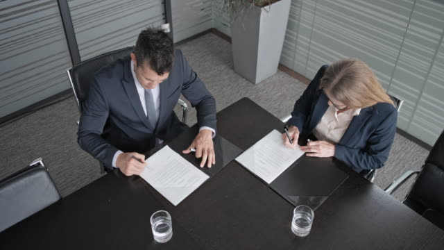 CS Asian businessman and Caucasian businesswoman signing a contract in the conference room and shaking hands Wide crane shot of an Asian businessman and Caucasian businesswoman with glasses sitting in conference room, signing a contract in the file folder on the table, exchanging them for a signature and shaking hands. Shot in Slovenia. exchanging stock videos & royalty-free footage