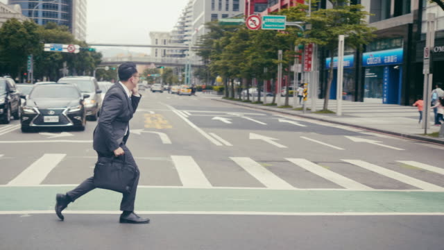 asian businessman crossing the street in a hurry and talking over the phone - chińczycy filmów i materiałów b-roll