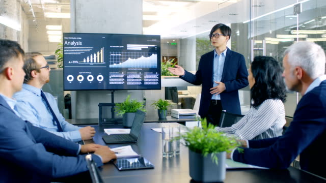 vídeos de stock e filmes b-roll de asian businessman gives report/ presentation to his business colleagues, pointing at the results showing statistics, pie charts and company's growth on wall tv screen. - fazer dinheiro