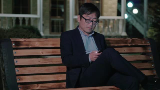 uomo d'affari asiatico nella notte park utilizza uno smartphone - corea video stock e b–roll
