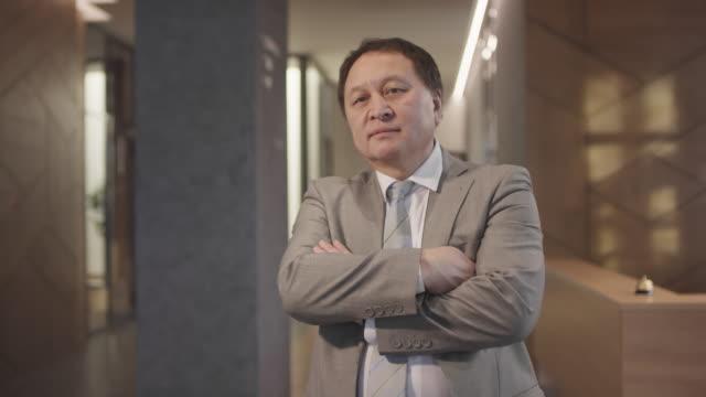 asian businessman posing in lobby of hotel - hotel reception filmów i materiałów b-roll
