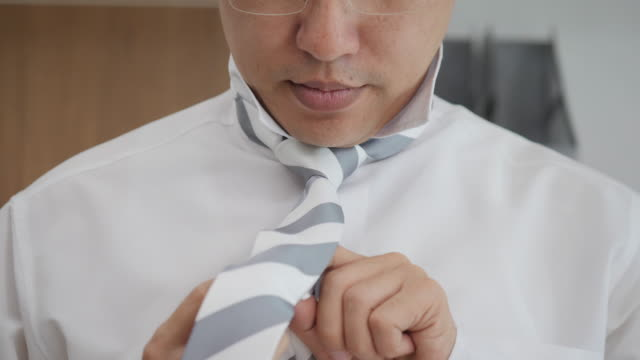 vídeos y material grabado en eventos de stock de empresario asiático prepara para el evento oficial, enderece el empate. nueva entrevista de trabajo, motivación del uno mismo, confianza, tratar de nudo de la corbata de moda. - corbata