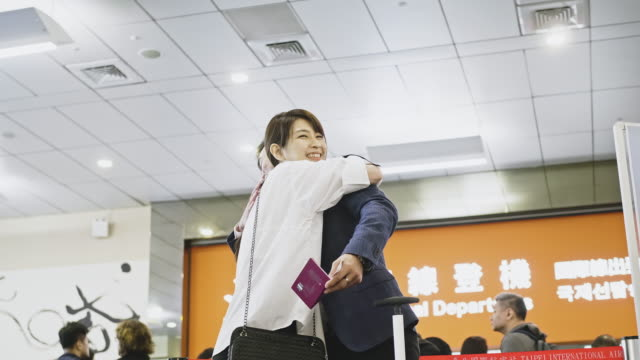 空港で妻に別れを告げるアジアのビジネスマン - 乗客点の映像素材/bロール