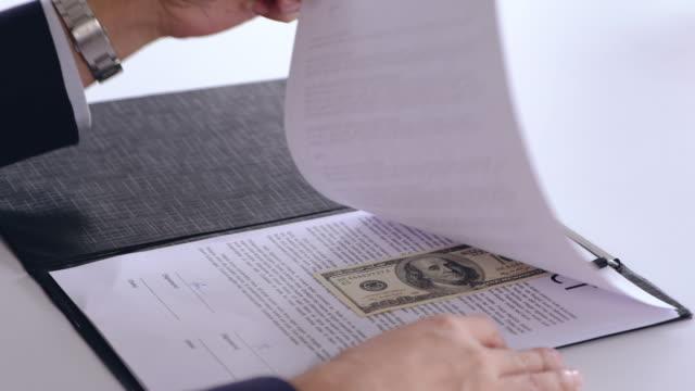 アジア系のビジネスマン記号契約ページを参照してください契約の賄賂のお金と彼に契約を通過する別の実業家。破損の概念。 - 腐敗点の映像素材/bロール