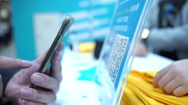 asiatische geschäftsmann mit smartphone für qr-code bargeldloses bezahlen zu scannen. scannen sie das zahlungssystem. business- oder technologiekonzept , scannen des sicherheits-qr-codes während der erbärmlichen covid-19 , neues normalkonzept - smartphone mit corona app stock-videos und b-roll-filmmaterial