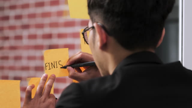Asian businessman wear suit looking and writing on sticky note for brainstorming ideas on clear whtieboard at modern office. analyze and synthesis project.back view