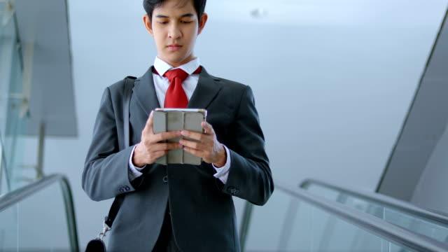 エスカレーターでタブレット コンピューターとアジア系のビジネスマン ビデオ
