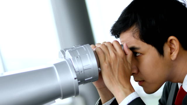 asian businessman with the binocular at the top of building video