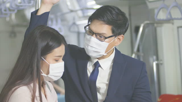 Asian businessmen and assistants discuss information in business negotiations while commuting on BTS or metro subway train wearing mask protection pandemic flu or virus covid-19. Behavior in public places during disease outbreaks. New normal lifestyle.