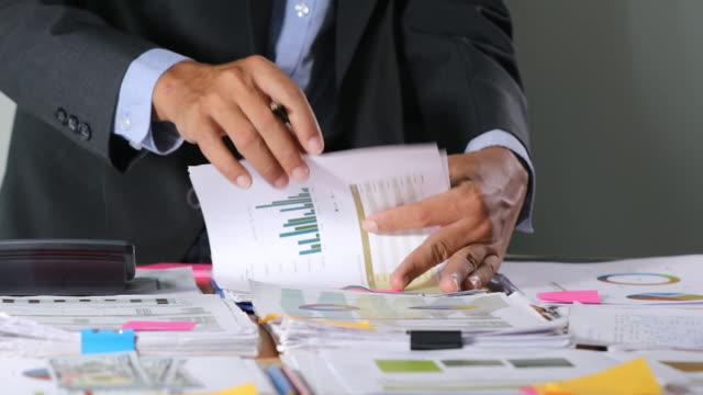 asiatiska affärs män använder kalkylatorer för analys projekt dokument och diagram finansiella diagram arbetar i bakgrunden på kontors bord - accounting bildbanksvideor och videomaterial från bakom kulisserna