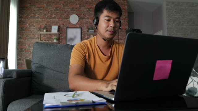 Asian businessmen is using notebook computers and wear headphones for online meetings and working from home. video