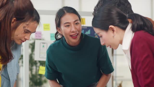 アジアのビジネスマンは、クリエイティブなwebデザイン計画アプリケーションに関するアイデアをブレインストーミングし、オフィスで協力する携帯電話プロジェクトのためのテンプレート� - クリエイティブな職業点の映像素材/bロール