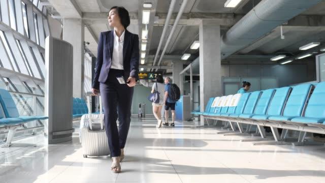 stockvideo's en b-roll-footage met aziatische zakenvrouw trekken koffer op de luchthaven, zakelijk reizen - zakenreis