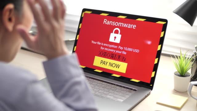 vidéos et rushes de ordinateur sérieux de femme d'affaires asiatique verrouillé par le ransomeware de virus sur son ordinateur portatif dans le bureau - virus informatique