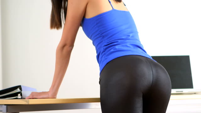 Asian businesswoman sexily standing by table