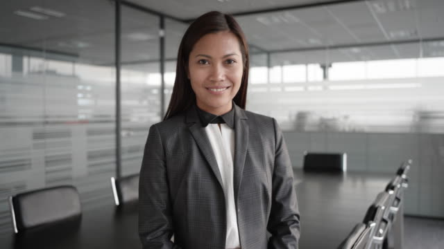 slo mo asian businesswoman smiling into the camera while standing in the conference room - professional woman stock videos & royalty-free footage