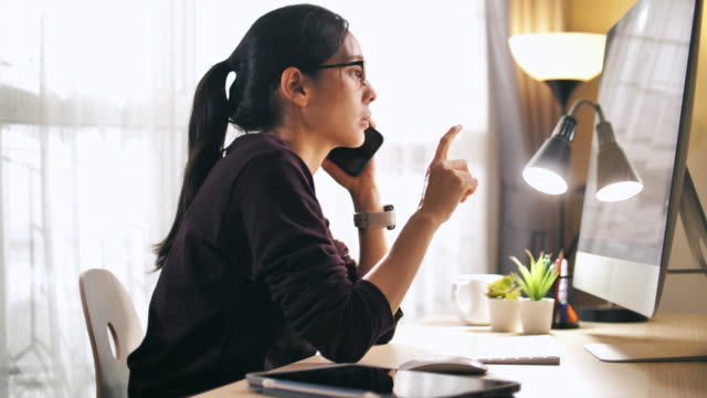 asian businesswoman talking on her mobile phone and working computer at home - rispondere video stock e b–roll