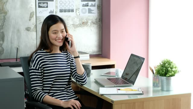 asian businesswoman talking on mobile phone while working in office. - owner laptop smartphone video stock e b–roll