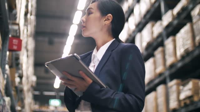 vídeos y material grabado en eventos de stock de mujer empresaria asiática que usa la tableta digital para comprobar la lista para el envío en almacén - suministros escolares