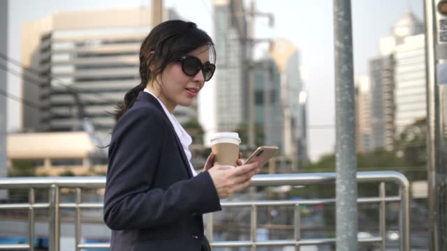 asian businesswoman using smart phone and talking in city - soft focus video stock e b–roll