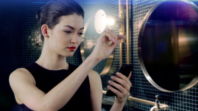 stockvideo's en b-roll-footage met aziatische zakenvrouw met behulp van slimme telefoon in elegante badkamer - cell phone toilet