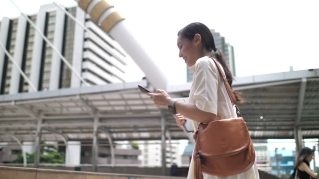 Asian Businesswoman using smart phone while walking to work