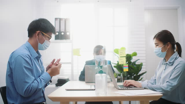 Asian Businesswoman wearing protective face mask and in the office using hand sanitizer during COVID-19