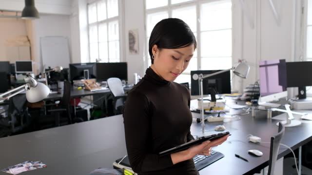 オフィスでデジタルタブレットを持つアジアのビジネスウーマン - 日本人のみ点の映像素材/bロール