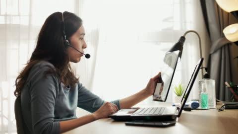 vídeos y material grabado en eventos de stock de asiática empresaria trabajando videollamada con su jefe en la tableta digital en casa - working from home
