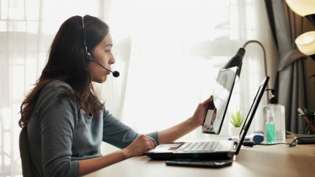 vidéos et rushes de femme d'affaires asiatique travaillant appel vidéo avec son patron sur la tablette numérique à la maison - workshop