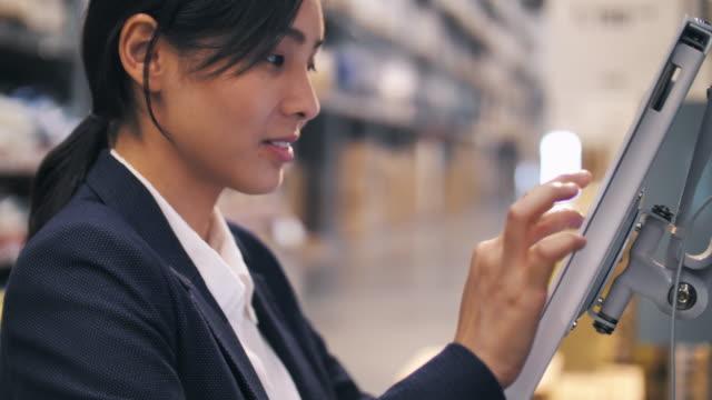 vídeos y material grabado en eventos de stock de empresaria asiática que trabaja con el tablet pc para comprobar el stock de productos en almacén - suministros escolares