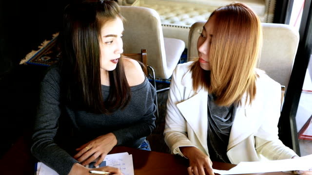 asian businesswomen working together on a laptop - two students together asian video stock e b–roll