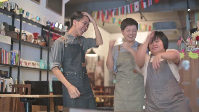 asian cafe down syndrome disability employee and owner dancing bonding time in cafe happily