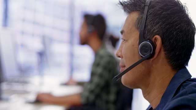 asian call center agent talking with a customer - supporto tecnico video stock e b–roll