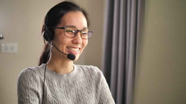 asian call center support her customer at home - słuchawki filmów i materiałów b-roll
