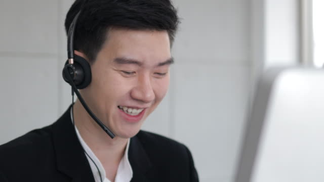 Asian call center wear headset and working with computer while consulting customer with online problem. support and operator service business representative concept