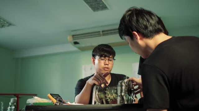 asian chief club of engineer advice engine beschreibt den betrieb der motorteile mit student engineering praktikant im labor. konzept von gadget, entwicklung und produktivität. - pflicht stock-videos und b-roll-filmmaterial