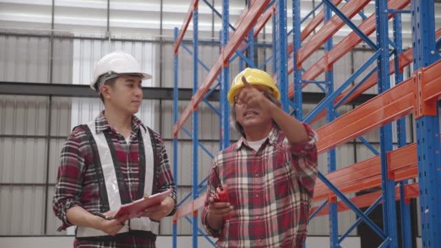 건설 공장이나 창고에서 일하는 것에 대해 이야기하는 아시아 수석 엔지니어 및 계약자. 걸어서 건물의 구조를 확인하십시오. 작업 하는 동안 착용 하는 안전 하드 모자 - 한 명의 중년 남자만 스톡 비디오 및 b-롤 화면