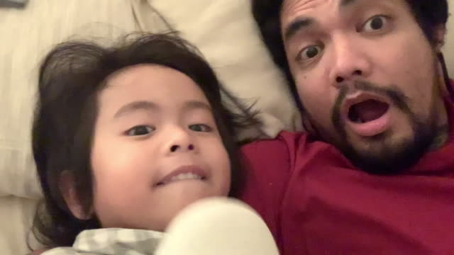 vidéos et rushes de enfant asiatique et homme hipster prenant le selfie avec l'appareil-photo de smartphone riant - photophone
