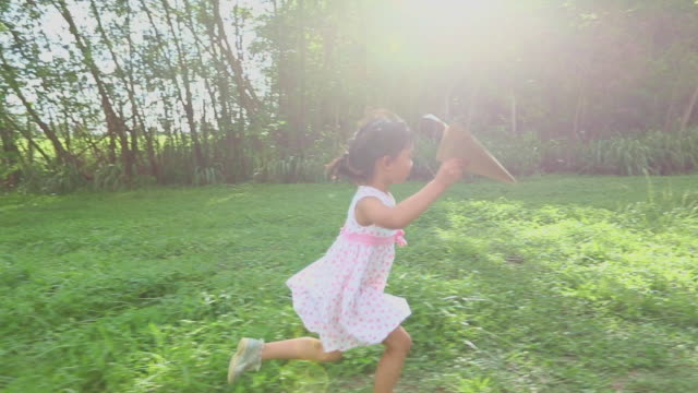 Asian child girl and father with a kite running and happy on meadow in summer in nature,slow motion video
