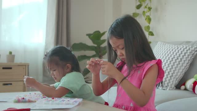 Asian child girl and friend threading beads onto a string together with intention and fun in home. Kid creating handmade bracelets to develop hand motility