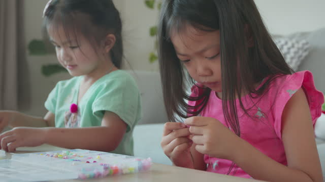 Asian child girl and friend threading beads onto a string together with intention and fun in home. Kid creating handmade bracelets to develop hand motility.