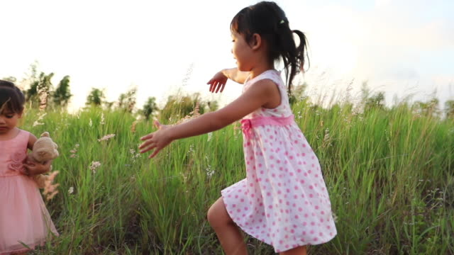 Asian child girl running and laughing happy on meadow in summer in nature