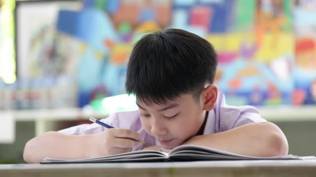 Asiatische Kinder im Studenten Uniform lesen und schreiben in der Schule Hausaufgaben. – Video