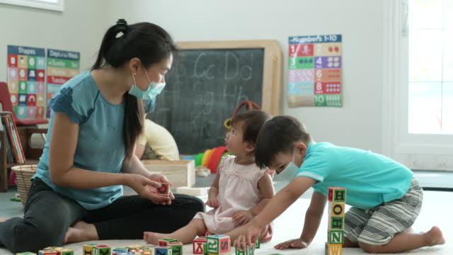 vídeos y material grabado en eventos de stock de niño asiático jugando con bloques en la guardería mientras usa máscaras - cuidado infantil