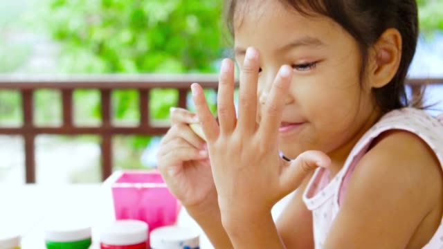 Asian childhood painting her hand in slow motion. Child crafts in leisure time. Video record in light nature and slow motion shot in 100 fps thai ethnicity stock videos & royalty-free footage