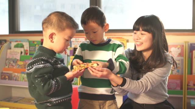 アジアのお子様に託児所の先生ピザを食べるのスクール形式 - 託児施設点の映像素材/bロール