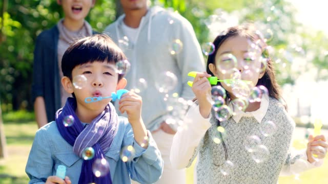 asian children blowing bubbles outdoors asian little girl and boy brother and sister blowing bubbles in park with parents watching from behind east asian culture stock videos & royalty-free footage