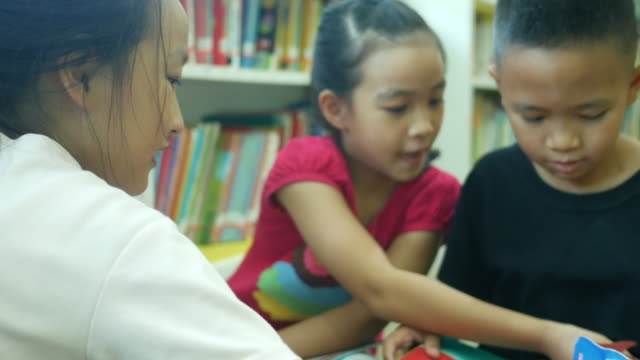 Asian children learning together in library